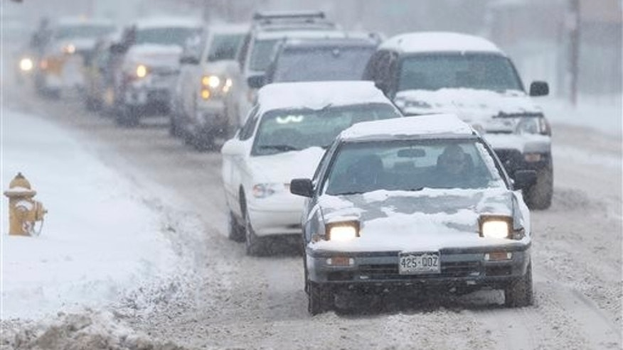 A line of vehicles slowed to a crawl during the snowstorm in Denver Tuesday.