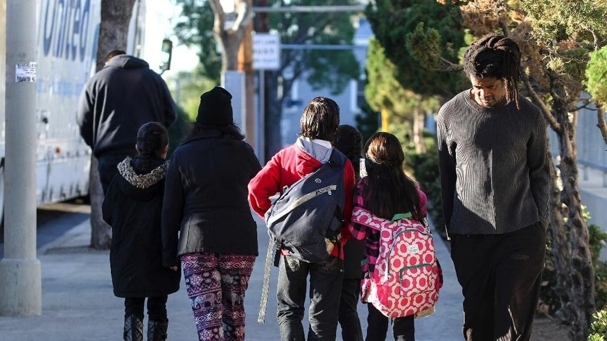 Parents pick up their children from school early, on Tuesday, Dec. 15, 2015, in Los Angeles. The nation's second-largest school district shut down Tuesday after a school board member received an emailed threat that raised fears of another attack like the deadly shooting in nearby San Bernardino. (AP Photo/Ringo H.W. Chiu)