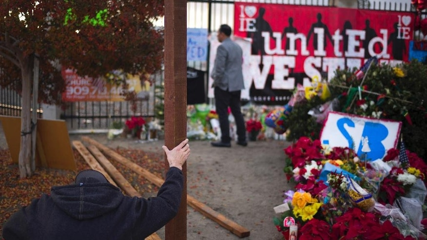 A man prays at a makeshift memorial near the Inland Regional Center, Friday, Dec. 11, 2015, in San Bernardino, Calif. Authorities said Syed Rizwan Farook and his wife Tashfeen Malikkilled shot and killed several people at a holiday gathering at the center on Dec. 2.  (AP Photo/Jae C. Hong)