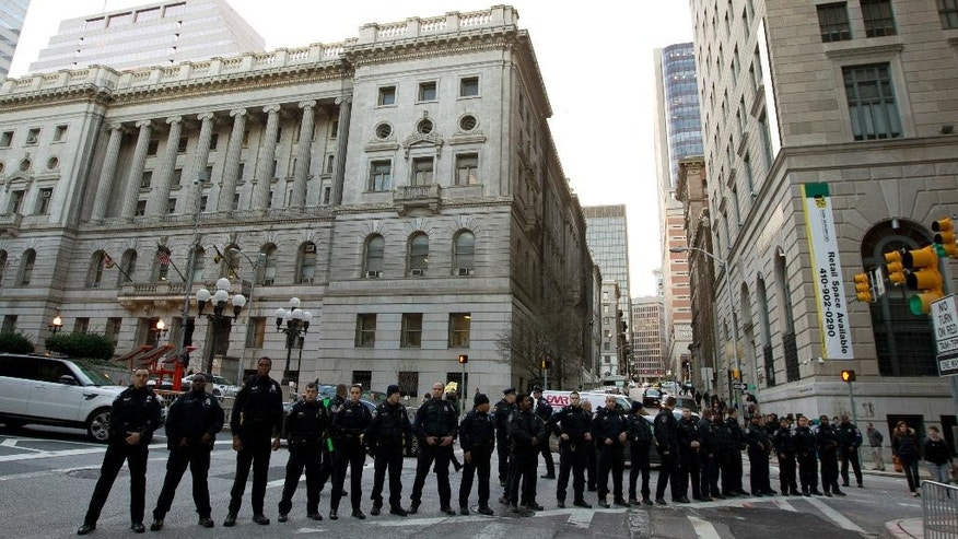 Baltimore police officers block the street in front of the courthouse after a mistrial was declared in the manslaughter trial of Officer William Porter, one of six Baltimore city police officers charged in connection to the death of Freddie Gray, on Wednesday, Dec. 16, 2015, in Baltimore.  (AP Photo/Jose Luis Magana)