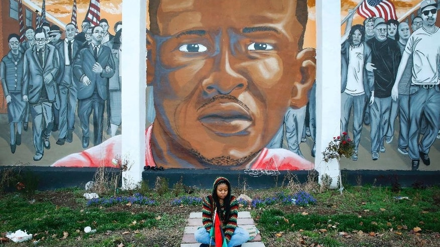 Jazmin Holloway sits below a mural depicting Freddie Gray at the intersection of his arrest, Wednesday, Dec. 16, 2015, in Baltimore. The first effort to find a police officer criminally responsible for Freddie Gray's death from a broken neck in a police van ended Wednesday with a hung jury and a mistrial. (AP Photo/Patrick Semansky)