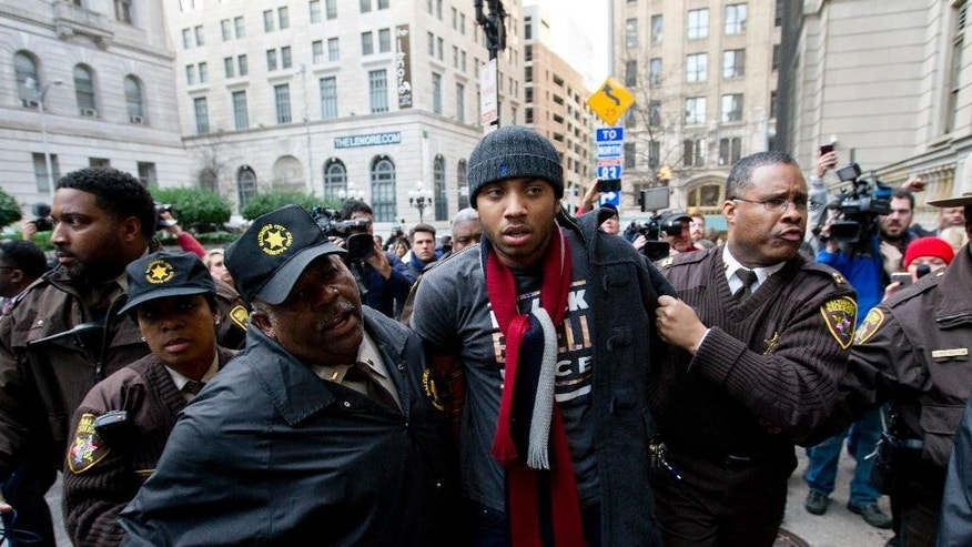 A demonstrator is detained outside of the courthouse after a mistrial of Officer William Porter, one of six Baltimore city police officers charged in connection to the death of Freddie Gray, on Wednesday, Dec. 16, 2015, in Baltimore. (AP Photo/Jose Luis Magana)