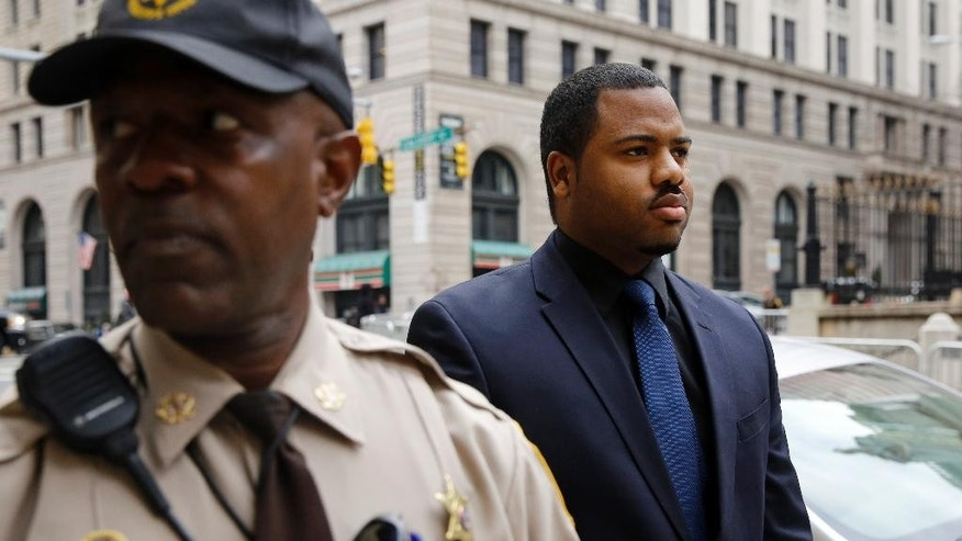 Officer William Porter, right, one of six Baltimore city police officers charged in connection to the death of Freddie Gray, walks into a courthouse during jury deliberations, Wednesday, Dec. 16, 2015, in Baltimore. Jurors failed to reach a verdict in the case and the judge declared a mistrial.  (AP Photo/Patrick Semansky)