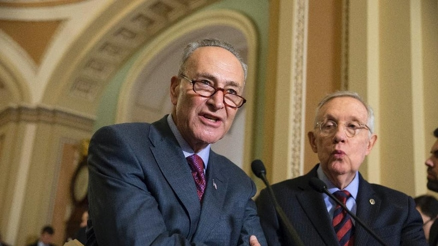 FILE - In this Dec. 8, 2015, file photo, Sen. Chuck Schumer, D-N.Y., joined by Senate Minority Leader Harry Reid, D-Nev., right, criticizes Republicans for not doing enough to stop gun violence, during a news conference on Capitol Hill in Washington. On Sunday, Dec. 13, 2015, Schumer joined Gov. Andrew Cuomo in calling on federal officials to set up a protocol to allow states access to the normally confidential FBI terrorism watch list. (AP Photo/J. Scott Applewhite, File)