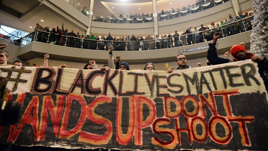 "FILE - In this Dec. 20, 2014 file photo, demonstrators chant, ""Black lives matter,"" to protest police, at the Mall of America rotunda in Bloomington, Minn."