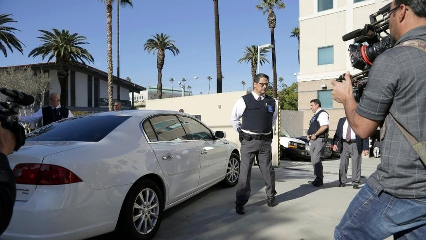 Security is tight as a car carrying Enrique Marquez Jr. arrives at U.S. District Court in Riverside, Calif., Thursday, Dec. 17, 2015. Marquez, a longtime friend of Syed Rizwan Farook, the male shooter in the San Bernardino terrorist attack, was charged today with conspiring with Farook in 2011 and 2012 to commit crimes of terrorism, and with the unlawful purchase of two assault rifles used in the deadly shooting two weeks ago.(AP Photo/Nick Ut)