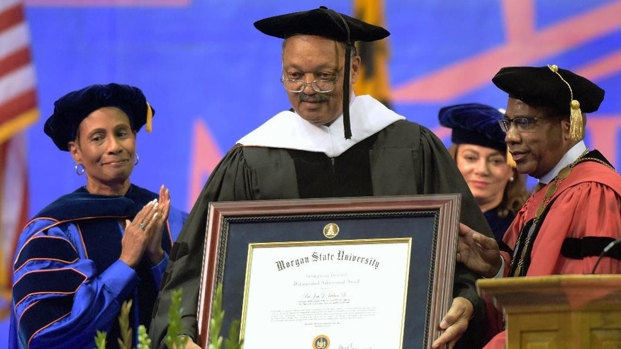 The Rev. Jesse Jackson, center, stands with Frances Draper, left, of Baltimore, a member of Morgan State University's board of regents, and David Wilson, right, university president, after receiving an honorary degree during the university's commencement exercises, Friday, Dec. 18, 2015, in Baltimore. The exercises commemorated the 50th anniversary of the Voting Rights Act of 1965. (AP Photo/Steve Ruark)