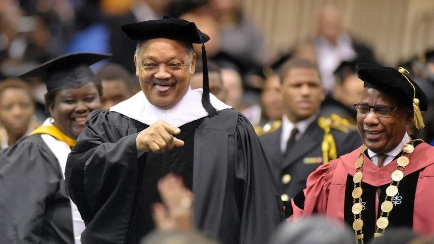 The Rev. Jesse Jackson, center, and David Wilson, right, president of Morgan State University, greet graduates and guests during the university's commencement exercises, Friday, Dec. 18, 2015, in Baltimore. The exercises commemorated the 50th anniversary of the Voting Rights Act of 1965. (AP Photo/Steve Ruark)