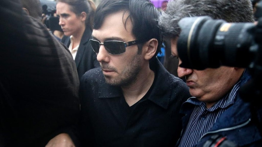 Martin Shkreli leaves the courthouse after his arraignment in New York, Thursday, Dec. 17, 2015. Shkreli, the former hedge fund manager vilified in nearly every corner of America for buying a pharmaceutical company and jacking up the price of a life-saving drug more than fiftyfold, was arrested Thursday on securities fraud charges unrelated to the furor. (AP Photo/Seth Wenig)