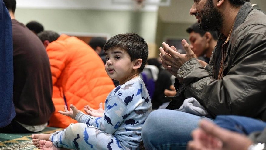 Salim Modak, right, and his son, Affan, pray at the All Dulles Area Muslim Society (ADAMS) Center in Sterling, Va., Friday, Dec. 18, 2015. (AP Photo/Sait Serkan Gurbuz)