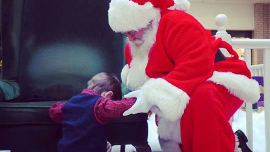 Prestyn Barnette, 4, prays for Baby Knox with Santa at South Carolina mall (Rebekah Lauren Sharpe)