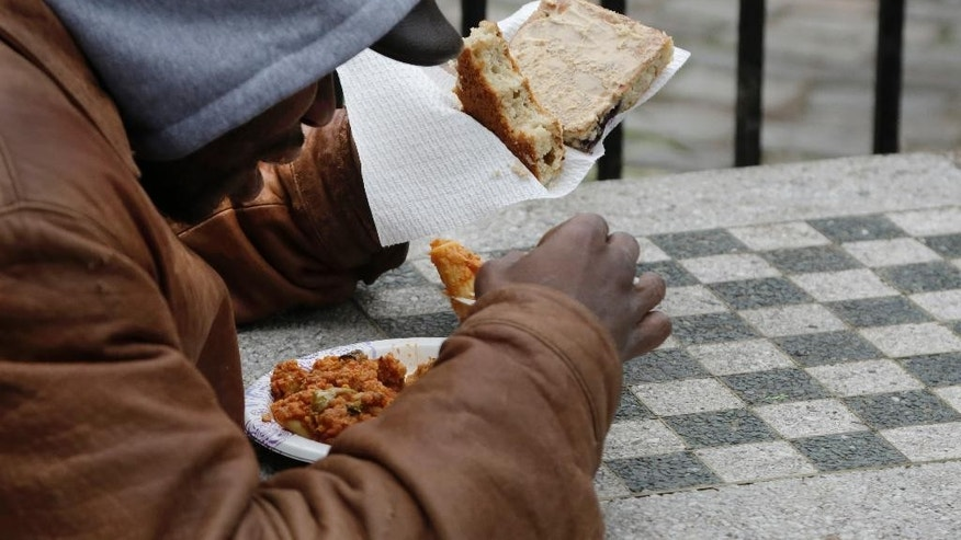A homeless man eats a free meal that was given to people gathered in Tompkins Square Park, Monday, Dec. 21, 2015 in New York. Homeless advocacy groups are threatening legal action against the city over its plans to conduct an aggressive homeless outreach program. The groups say they fear police involvement in the campaign will result in more arrests of homeless people. (AP Photo/Mark Lennihan)