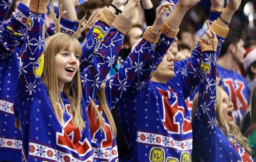Wearing ugly Christmas sweaters, Kansas fans cheer during the during the first half of an NCAA college basketball game against Montana Saturday, Dec. 19, 2015, in Lawrence, Kan. Kansas won the game 88-46. The school attempted to set a Guinness world record for the largest gathering of people wearing ugly holiday sweaters. (AP Photo/Charlie Riedel)