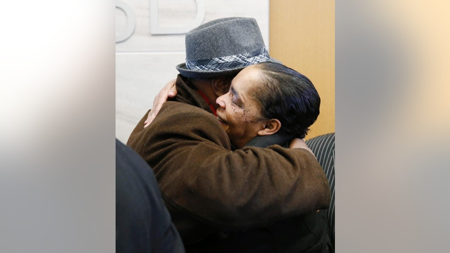 Rev. Terrence Hughes, left, hugs Stephanie Burke after a judge set bond at $50,000 for Burke's husband, Clarence Moses-EL, during a hearing early Tuesday, Dec. 22, 2015, in Denver. Moses-EL was convicted of rape in 1988 after the victim said his face came to her in a dream but he has maintained his innocence. Moses-EL is expected to be released from custody Tuesday. (AP Photo/David Zalubowski)