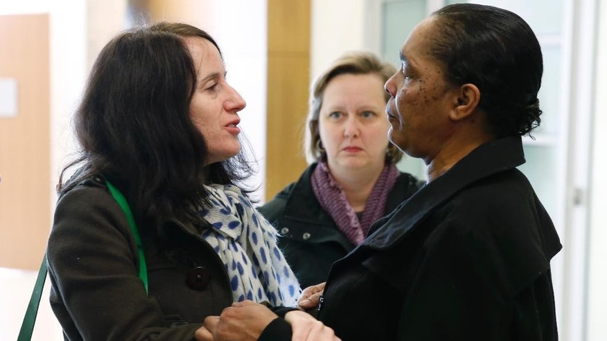 Susan Greene, left, congratulates Stephanie Burke after a judge set bond at $50,000 for Burke's husband, Clarence Moses-EL, during a hearing early Tuesday, Dec. 22, 2015, in Denver. Moses-EL was convicted of rape in 1988 after the victim said his face came to her in a dream but he has maintained his innocence. Moses-EL is expected to be released from custody Tuesday. (AP Photo/David Zalubowski)