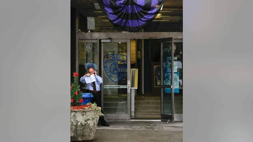 A purple and black bunting hangs over the entrance to the 50th precinct of the New York Police Department, Tuesday, Dec. 22, 2015, in New York. Detective Joseph Lemm, a 15-year veteran of the NYPD, was one of six American service members killed Monday in Afghanistan when an attacker rammed an explosives-laden motorcycle into their patrol. (AP Photo/Julie Jacobson)