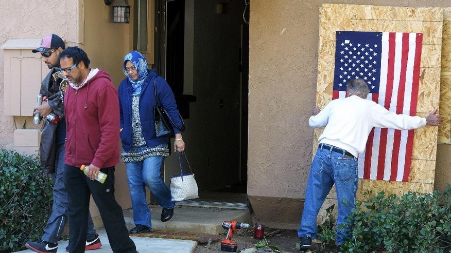 FILE - In this Dec. 19, 2015, file photo, Syed Rizwan Farook's brother Syed Raheel Farook, left, brother-in-law Farhan Khan, second from left, and mother, Rafia Farook, third from left, leave the house of the husband and wife who killed 14 people in San Bernardino, Calif., as landlord Doyle Miller prepares to board up the property in Redlands, Calif. The family was removing items from the couple's home. Since the attack, Rafia Farook, 62, has emerged as a mysterious figure; someone close to her son, yet according to family attorneys utterly unaware of his terrorist plans or that he had turned the townhome garage in a makeshift bomb-making facility. (Will Lester/The Inland Valley Daily Bulletin via AP, File)  MANDATORY CREDIT