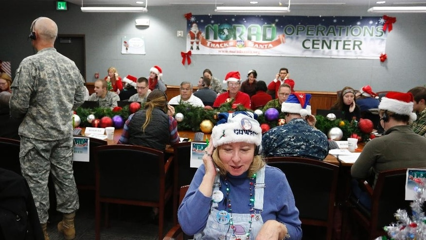 FILE - In this Dec. 24, 2014, file photo, volunteer Patty Shook takes a phone call from a child asking where Santa is and when he will deliver presents to her home, inside a phone-in center during the annual NORAD Tracks Santa Operation, at the North American Aerospace Defense Command, at Peterson Air Force Base, Colo. Patty and her husband, Bryan, who is retired from the Air Force, have been volunteering at NORAD each Christmas Eve for five years, fielding calls from children from all over the world eager to hear about Santa's progress. (AP Photo/Brennan Linsley)