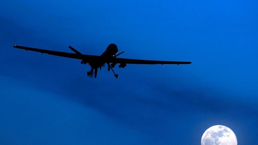 FILE - In this Jan. 31, 2010 file photo, an unmanned U.S. Predator drone flies over Kandahar Air Field, southern Afghanistan, on a moon-lit night.  Putting the U.S. military in charge of drone strikes in Iraq and Syria is leading to reduced congressional scrutiny.   Some officials and activists fear that means a greater risk of civilian casualties.   (AP Photo/Kirsty Wigglesworth, File)