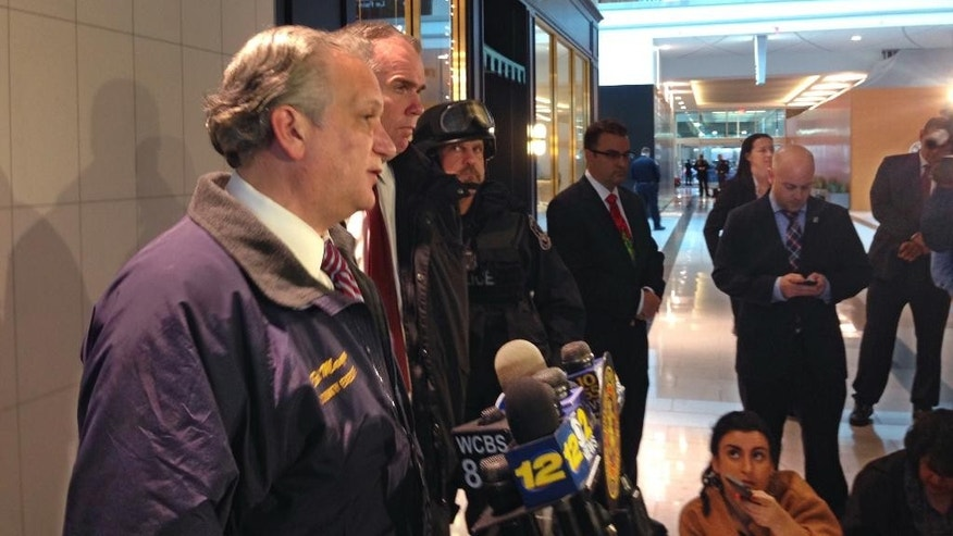 Nassau County Executive Edward Mangano, left, addresses the media after a person was shot inside the Roosevelt Field Mall, in Garden City, N.Y., Tuesday, Dec. 22, 2015. Police say a worker was shot during an attempted robbery at a Rolex dealer inside the Long Island mall filled with Christmas shoppers and a suspect was in custody. (AP Photo/Frank Eltman)