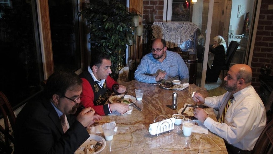 In this Dec. 9, 2015 photo, Namee Barakat, left foreground, and his brother-in-law, Mohammad Abu-Salha, right, chat with relatives during dinner at the Barakat home in Raleigh, N.C. The two families were united in tragedy when Barakat's son and Ab-Salha's two daughters were gunned down by a disgruntled neighbor last February. (AP Photo/Allen G. Breed)