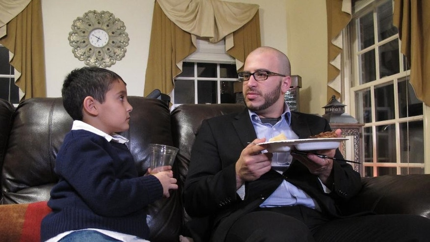 "In this Dec. 9, 2015 photo, Farris Barakat talks with his cousin, Ameer Bamyeh, left, during a family dinner at the Barakat home in Raleigh, N.C. When Barakat asked the boy what he thought of Republican presidential candidate Donald Trump's plan to bar most Muslims entering the country, Ameer replied: ""I like Obama better."" (AP Photo/Allen G. Breed)"