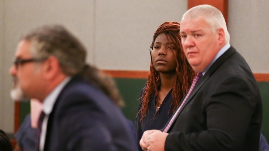 Lakeisha Nicole Holloway, center, appears with her public defenders Joseph Abood, left, and Scott Coffee in district court for her arraignment Wednesday, Dec. 23, 2015, in Las Vegas. Holloway, who crashed her car into pedestrians on the Las Vegas Strip on Sunday, Dec. 20, has been charged with murder, child abuse and hit-and-run. (AP Photo/Chase Stevens)