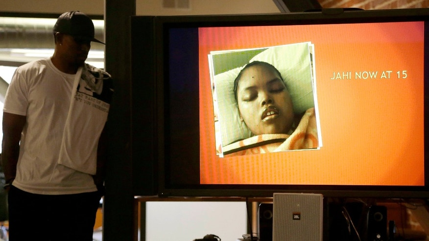 Dec. 23, 2015: A recent photo of Jahi McMath is shown on a video screen next to her uncle Timothy Whisenton at a news conference in San Francisco.