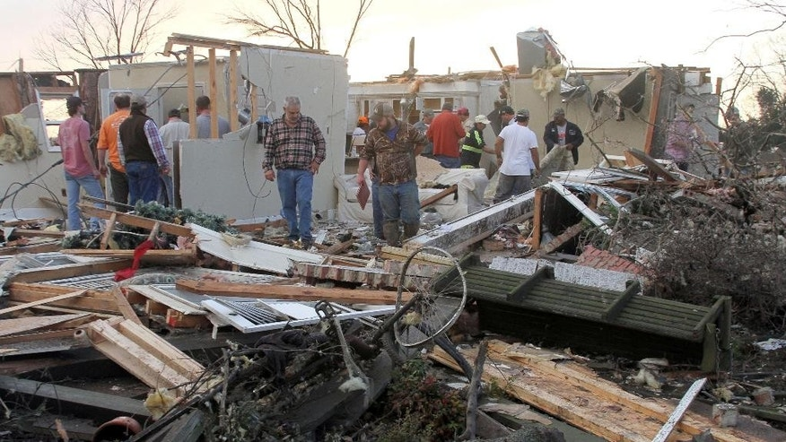 "People inspect a storm-damaged home in the Roundaway community near Clarksdale, Miss., Wednesday, Dec. 23, 2015. A storm system forecasters called ""particularly dangerous"" killed multiple people as it swept across the country Wednesday. (Troy Catchings/The Press Register via AP) MANDATORY CREDIT"