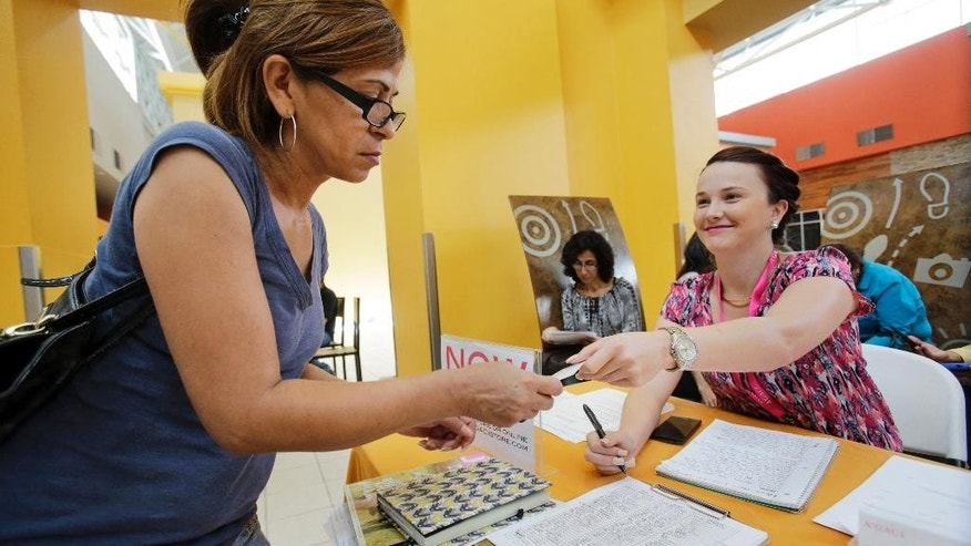 In this Tuesday, Oct. 6, 2015, photo, A'GACI clothing store hiring manager Marcie Lowe, right, gives her card to job applicant Xionara Garcia, left, of Miami, during a job fair at Dolphin Mall in Miami. According to the Labor Department on Thursday, Dec. 24, 2015, the number of Americans seeking unemployment benefits fell the week before, reflecting a job market that continues to look persistently healthy. (AP Photo/Wilfredo Lee)