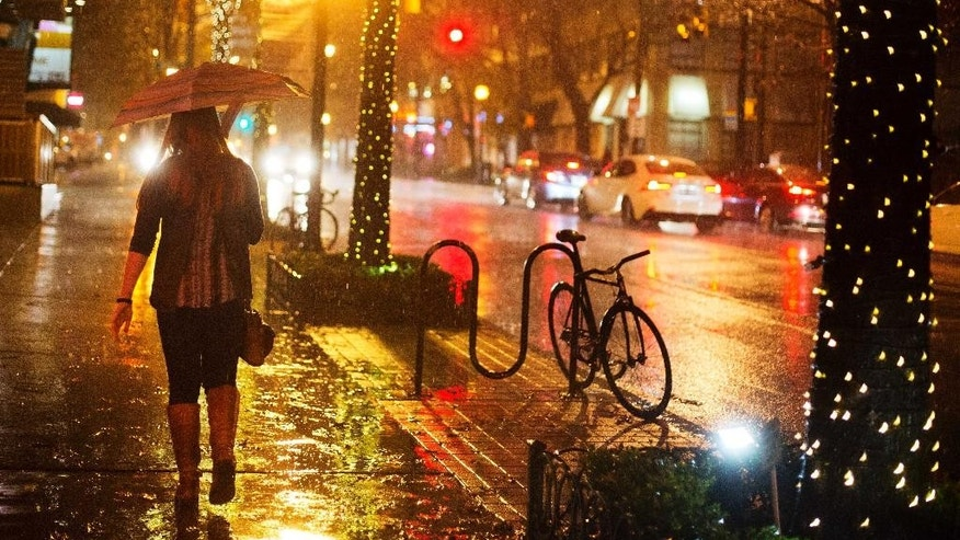 A person walks in midtown Atlanta, Wednesday, Dec. 23, 2015. In parts of Georgia, including Atlanta, a flood watch was posted through Friday evening, the National Weather Service said. (AP Photo/David Goldman)