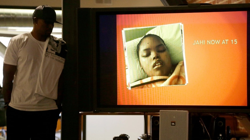 Jahi McMath is shown on a video screen next to her uncle Timothy Whisenton during a news conference.