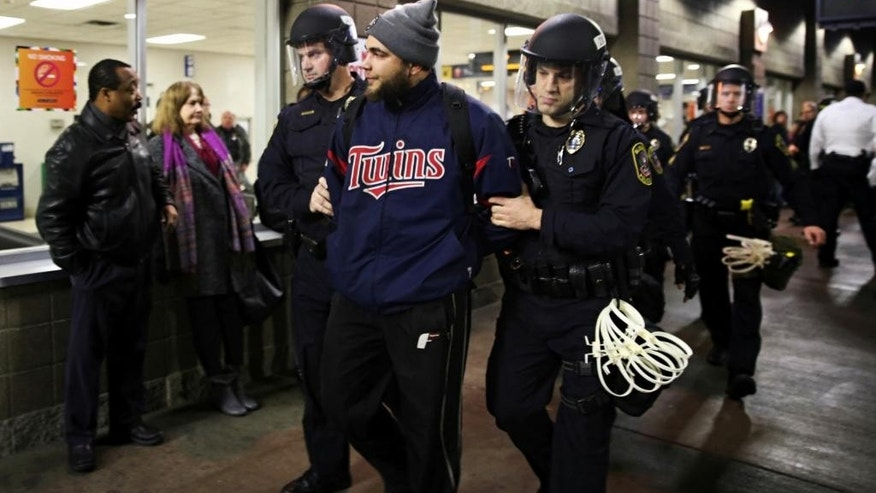 Law enforcement detained a protester at the Mall of America. A large protest that started at the Mall of America quickly migrated Wednesday, Dec. 23, 2015, to Minneapolis-St. Paul International Airport, where demonstrators blocked roads and caused significant traffic delays. (Leila Navidi/Star Tribune via AP)