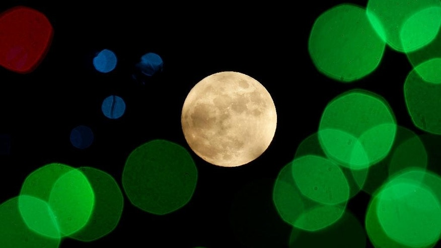 The nearly-full moon is seen among Christmas lights at a holiday display Thursday, Dec. 24, 2015, in Lenexa, Kan. When the moon turns full, at 5:11am cst., it will be the first full moon to fall on Christmas day since 1977. Named the Long Night Moon because it's the first full moon to follow the winter solstice, it's also known as the Cold Moon. (AP Photo/Charlie Riedel)