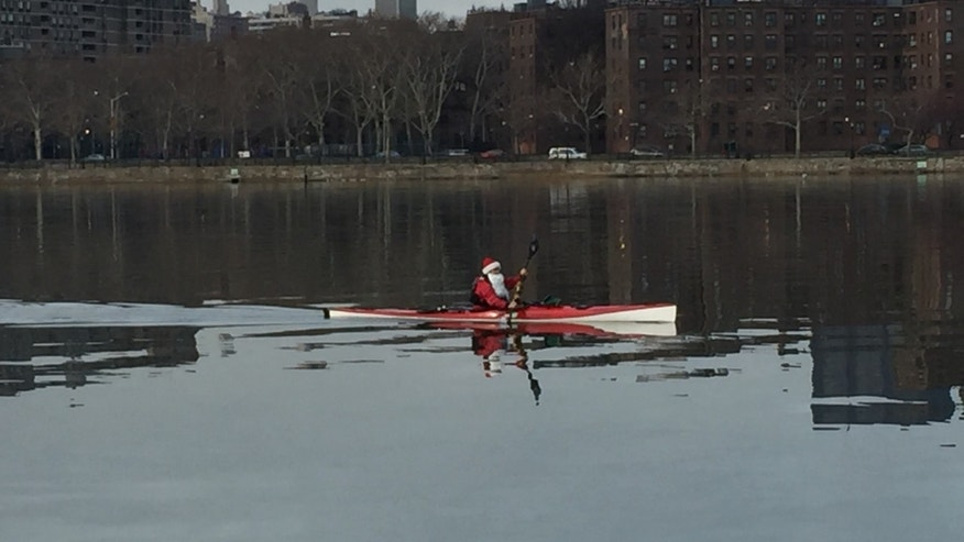 A kayaker in a Santa suit on the East River outside New York City.