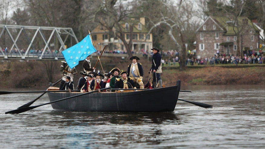 John Godzieba, standing second from right, portraying Gen. George Washington, looks towards New Jersey from a Durham boat during a re-enactment of Washington's historic crossing of the Delaware River, Friday, Dec. 25, 2015, in Washington Crossing, Pa. (AP Photo/ Joseph Kaczmarek)