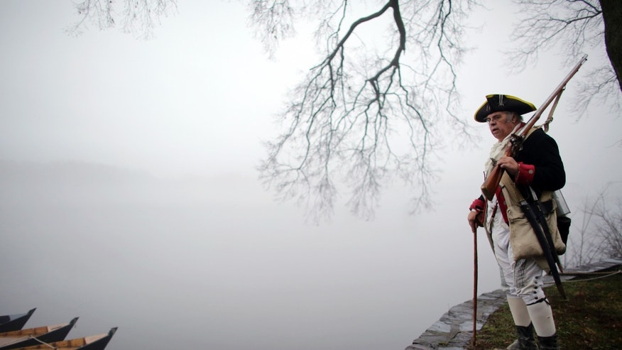 Revolutionary War re-enactor Bill Strunk looks at the fog covering the river before the re-enactment of Washington crossing the Delaware River, Friday, Dec. 25, 2015, in Washington Crossing, Pa.  (AP Photo/ Joseph Kaczmarek)