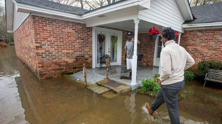 Gregory Shuford, left, and Terease Shuford keep an eye on flooding in west Montgomery, Ala., on Christmas morning Friday, Dec. 25, 2015. The line of severe storms continued marching eastward Thursday, dumping torrential rain that flooded roads in Alabama and caused a mudslide in the mountains of Georgia. (Mickey Welsh/The Montgomery Advertiser via AP) MANDATORY CREDIT