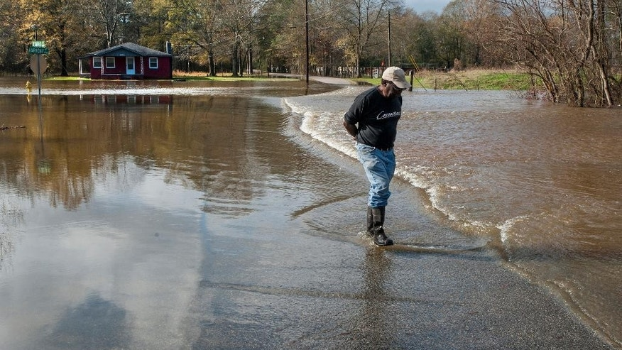 Barron Pinkney walks along a flooded section of Harmony Street in west Montgomery, Ala., on Christmas morning Friday, Dec. 25, 2015. The line of springlike storms continued marching east Thursday, dumping torrential rain that flooded roads in Alabama and caused a mudslide in the mountains of Georgia. (Mickey Welsh/The Montgomery Advertiser via AP) MANDATORY CREDIT