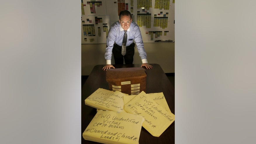In this Thursday, Dec. 3, 2015, photo, Cook County Sheriff's Detective Jason Moran poses for a portrait with his case files of unidentified victims of serial killer John Wayne Gacy in Maywood, Ill.
