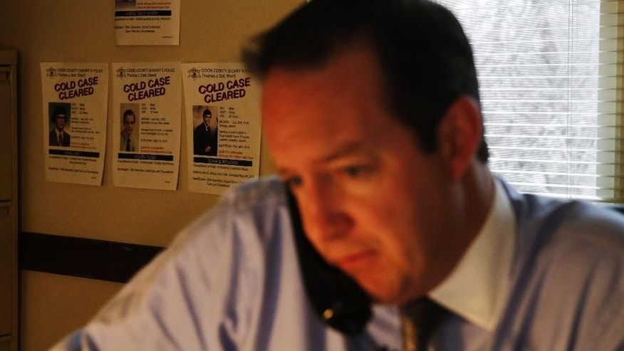 In this Thursday, Dec. 3, 2015, photo, Cook County Sheriff's Detective Jason Moran works in his office in Maywood, Ill., near small posters of cold cases that were cleared by him during his investigation of unidentified murder victims of John Wayne Gacy.
