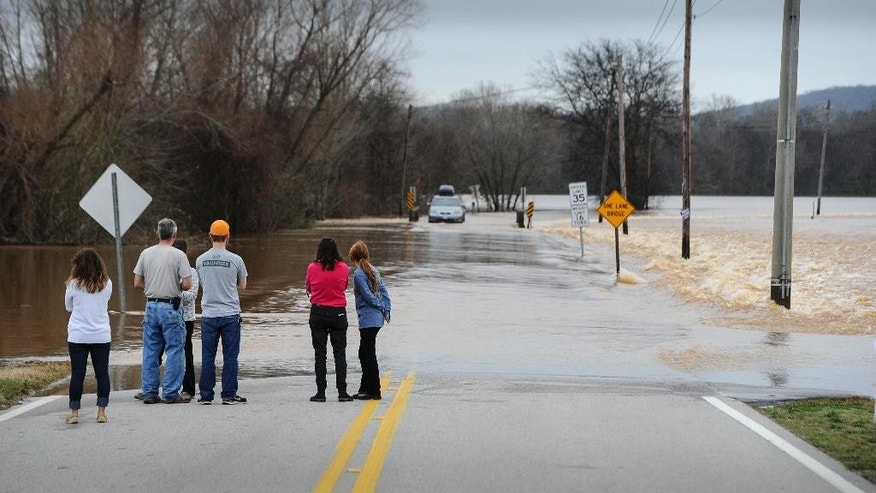 Bystanders watch the Flint River flow over Old Hwy. 431 on Saturday, Dec. 26, 2015, in Owens Cross Roads, near Huntsville, Ala. The flooding is the result of heavy downpours that have been thrashing the southeastern U.S. since Wednesday, bringing record rainfalls in some areas. (AP Photo/John Amis)