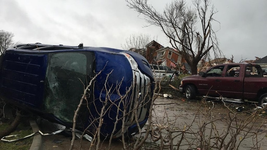 Damage of vehicles and houses are seen after Saturday's tornado spread out in Rowlett, Texas, Sunday, Dec. 27, 2015. At least 11 people died and dozens were injured in apparently strong tornadoes that swept through the Dallas area and caused substantial damage this weekend. (AP Photo/David Warren)