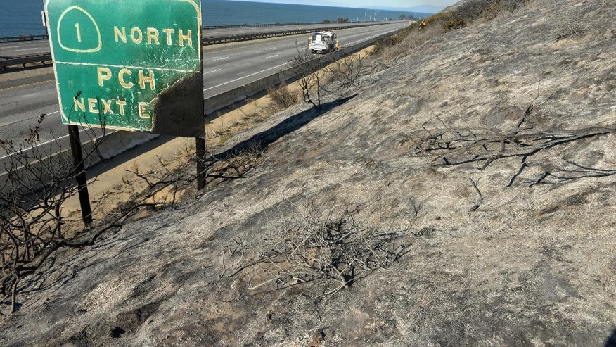 Parked on a closed US Highway 101, a Santa Barbara County Fire Department fire engine and crew douse a hot spot while working a Solimar wildfire in Ventura County, Calif. on  Saturday, Dec. 26, 2015. The fire, which began on Christmas night, has charred 1,200 acres. (Mike Eliason/Santa Barbara County Fire Dept. via AP)