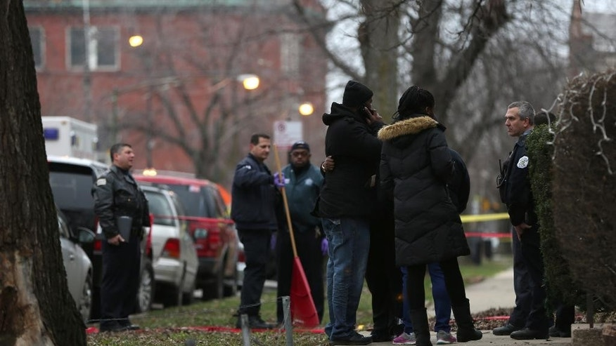 Chicago police officers talk with relatives of one of the two people killed by a police officer, as they investigate a shooting in the entry of their apartment in Chicago on Saturday, Dec. 26, 2015. A Chicago police officer shot and killed two people while responding to a domestic disturbance call in the neighborhood on the city's West Side, police said. (Abel Uribe/Chicago Tribune via AP)