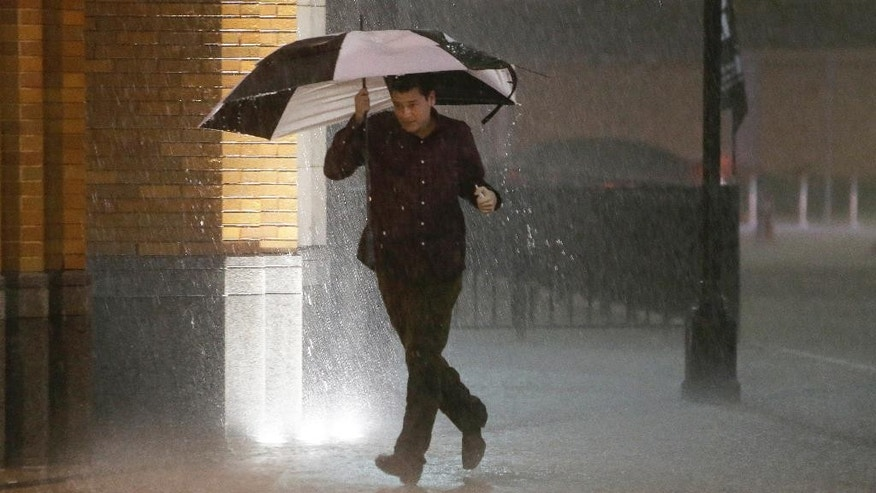 A man runs as sirens sound during a severe storm over downtown Dallas, Saturday, Dec. 26, 2015, in Dallas. The National Weather Service said the Dallas area was under a tornado warning Saturday. (AP Photo/LM Otero)