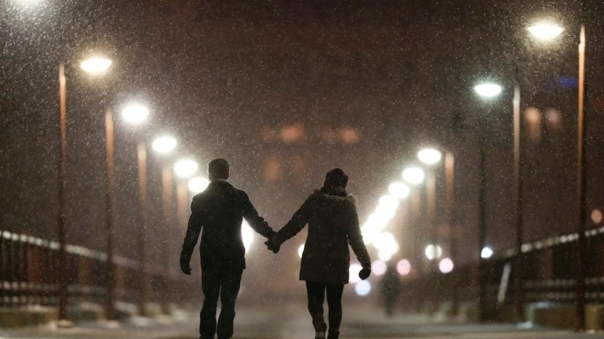 Peter Best and Mackenzie Kuhl hold hands while walking across the Stone Arch Bridge, Monday, Dec. 28, 2015, in Minneapolis. A winter storm is expected to dump up to a foot of snow in south-central Minnesota before it tracks north and east. (Jeff Wheeler/Star Tribune via AP)  MANDATORY CREDIT; ST. PAUL PIONEER PRESS OUT; MAGS OUT; TWIN CITIES LOCAL TELEVISION OUT