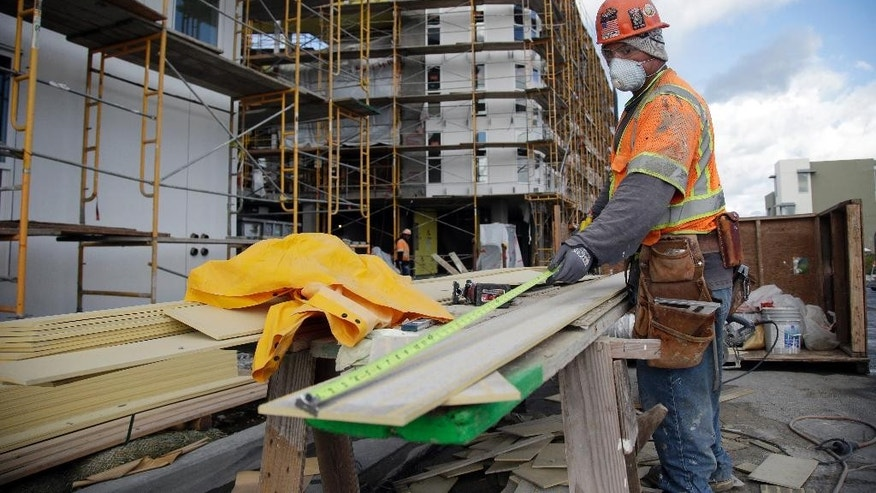 In this Nov. 9, 2015, photo, a worker makes measurements at the new San Francisco Shipyard homes development in the Bayview Hunters Point district in San Francisco. As San Francisco rides a massive building boom, fueled largely by growth in tech-based jobs, many African-Americans worry they will not be able to afford to stay in a neighborhood they've long called home. (AP Photo/Marcio Jose Sanchez)