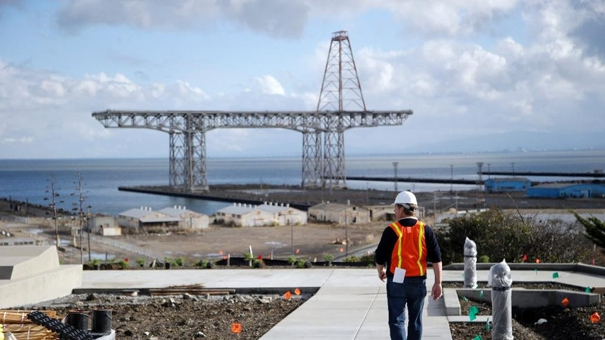 In this Nov. 9, 2015, photo, with the area's historic shipyard in the background, David Satterfield, spokesman for lead developer Lennar Urban, walks the grounds of the new San Francisco Shipyard homes development in the Bayview Hunters Point district in San Francisco. (AP Photo/Marcio Jose Sanchez)
