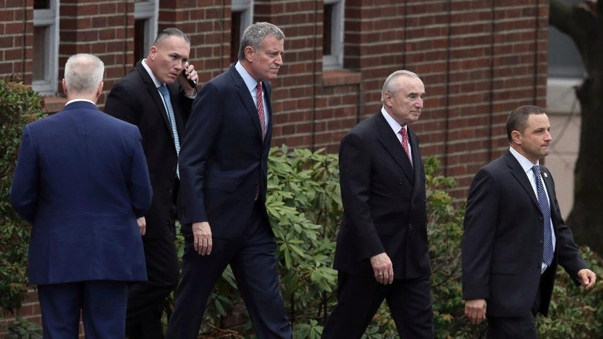 New York City Mayor Bill de Blasio, center, and Police Commissioner William Bratton, second from right, leave a service for Joseph Lemm in West Harrison, N.Y., Tuesday, Dec. 29, 2015. Lemm, who was a technical sergeant in the Air Guard's 105th Base Security Squadron and a 15-year veteran of the NYPD, was killed when his patrol was attacked by a suicide bomber outside Bagram Air Base in Afghanistan. (AP Photo/Seth Wenig)